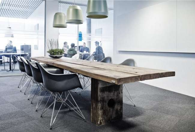 Gaia plank table with a rustic surface in a meeting room with Eames Chair